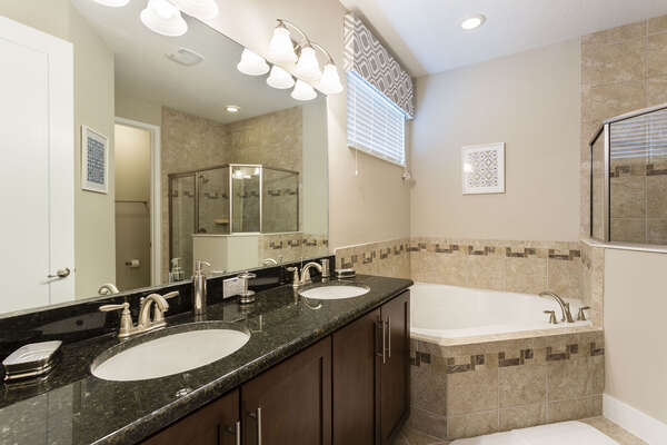 The en-suite bathroom features dual vanity, garden tub, and walk-in shower
