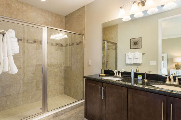 The en-suite bathroom features a glass door walk-in shower with dual vanity