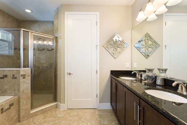 An en-suite bathroom with walk-in shower, dual vanity, and garden tub