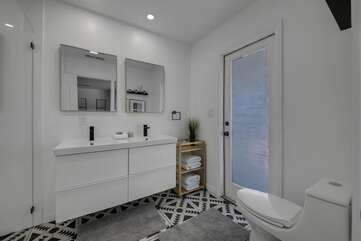 The Private, en suite bathroom features a tile shower and double vanity sinks