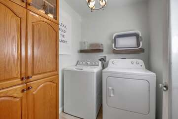 Fully equipped laundry room with washer, dryer, ironing board, and iron.