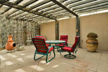 Patio with table and chairs, clay fire pit, and shade.