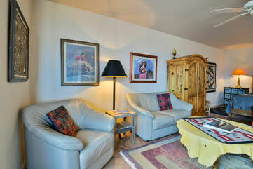 Living room of this Moab place to stay, with multiple loveseats, wardrobe, and coffee table.