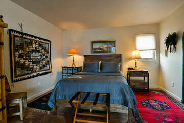 Sleeping space of this Moab place to stay, with large bed, wall-hanging weave, and wooden side table.
