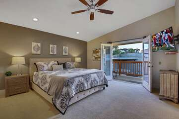 The Master Suite 1 is located upstairs at the end of the hallway, featuring a Cal King-sized Bed, 48-inch Samsung Smart television; access to the back deck patio and a private, en suite bathroom.