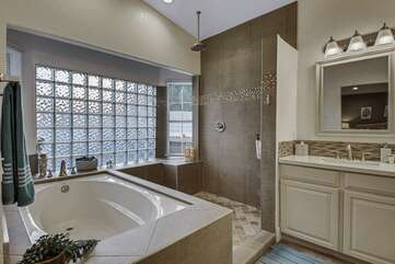 Private, en suite bathroom features a soaking tub, tile shower and two vanity sinks and a vanity with a mirror.