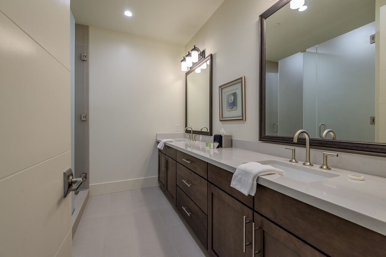 Upper Level Full Shared Bath with Dual Stone Counter Sinks and a Tile/Glass Shower