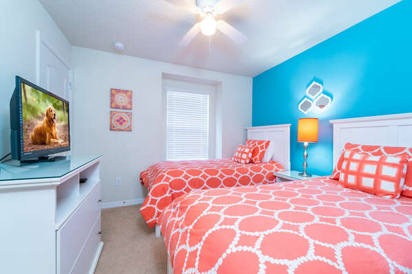 Bright bedroom with 2 twin beds showing the TV
