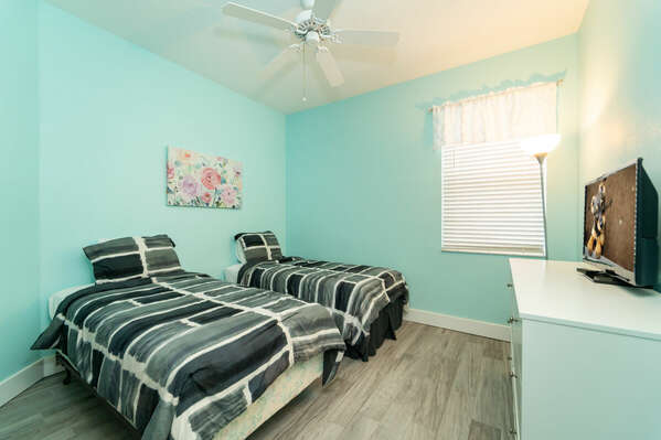 Bedroom 3 has twin beds and a flatscreen TV