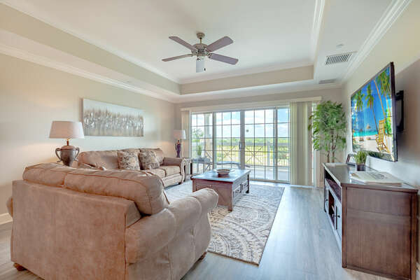 The living area has comfortable seating, a large TV and and access to the private balcony