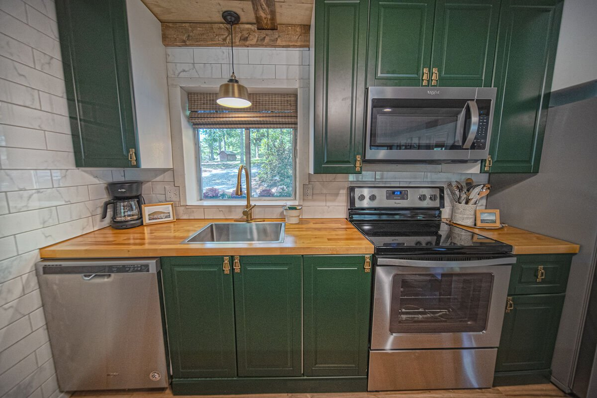 Stainless steel appliances in the kitchen surrounded by green painted cabinetry.