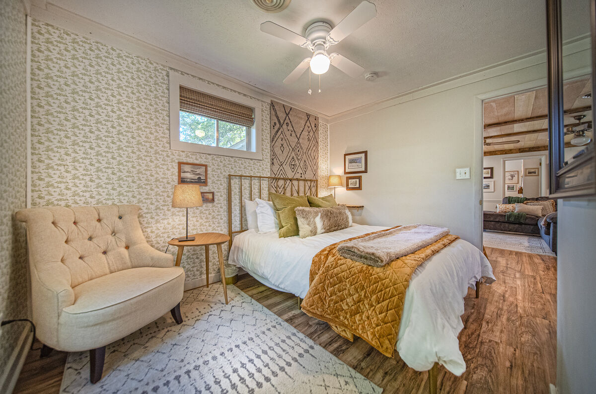 Small love seat and twin nightstands around a large bed.