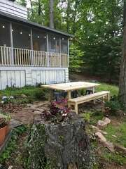 The back yard of this waterfront Smith Mountain Lake vacation rental, with a picnic table and bench.