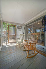 Screened porch with two rocking chairs.