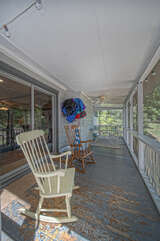Screened porch with seating.
