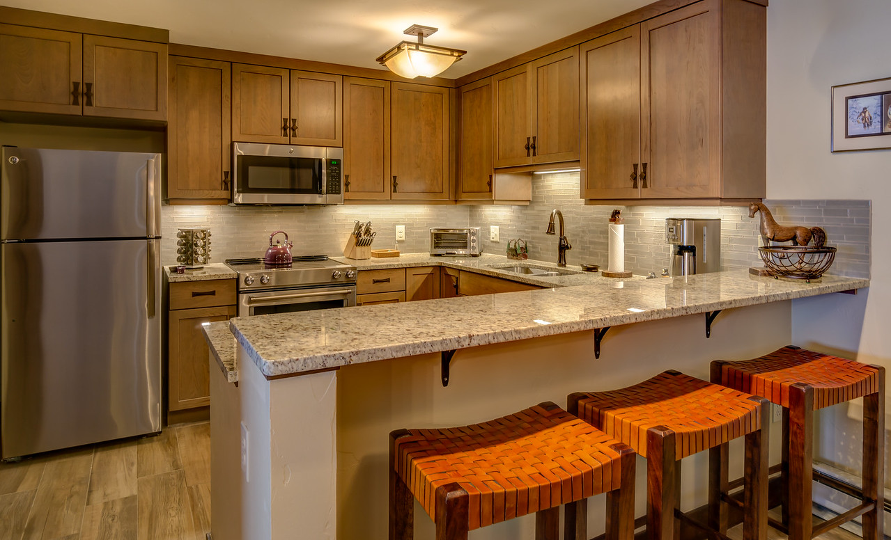 Kitchen with seating by the breakfast counter, fridge, and microwave above oven range.