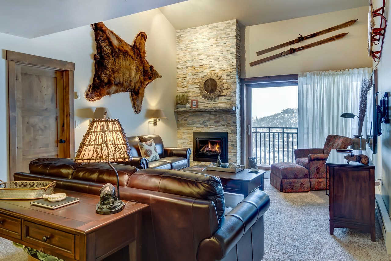 Rustic style living room with bear skin and skis hung on walls. Leather couches and featuring white brick fireplace.