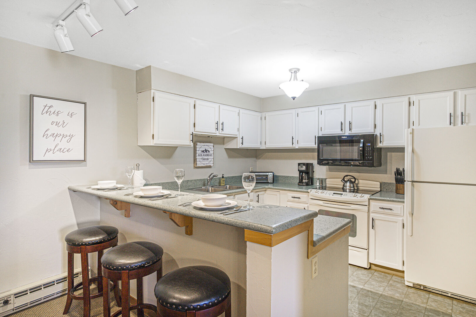 Kitchen with three stools at a gray counter. White cabinets with built-in microwave.