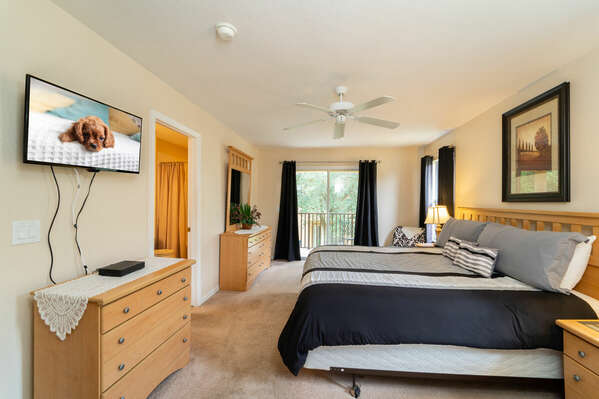 Master bedroom (upstairs) with king bed, balcony and wall mounted TV