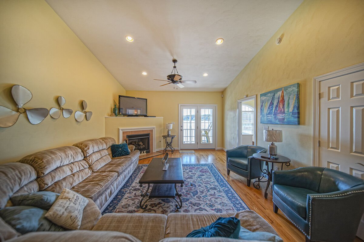 Large Open Living Area with sectional couch, two armchairs, and TV above a fireplace.