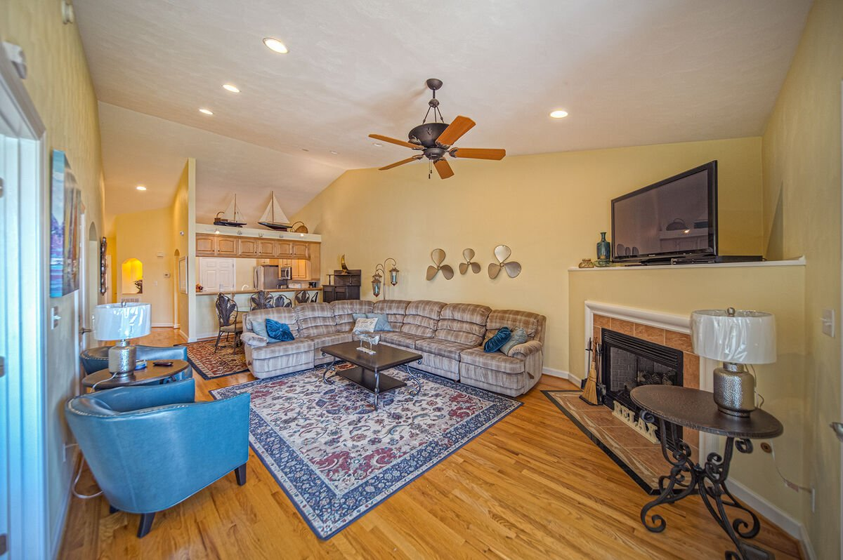 TV sits above a fireplace in the living area near a large sectional couch.