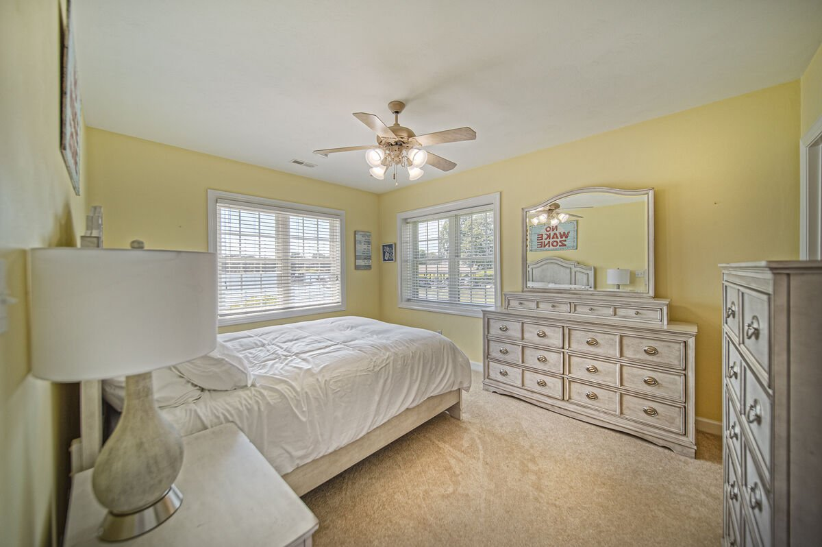 Lower Level Master with En Suite, large bed, and vanity dresser, Overlooking the Lake.