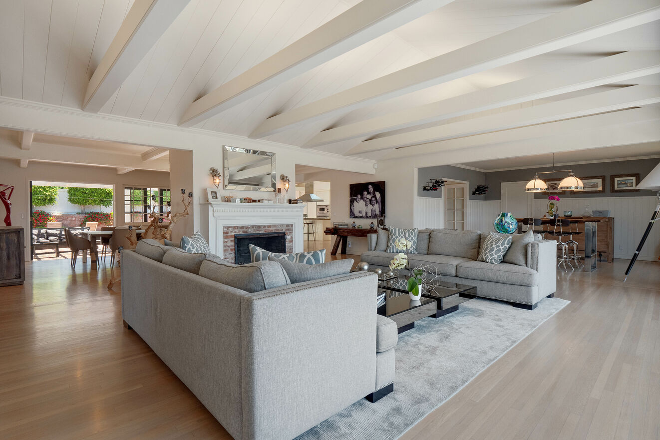 Formal living room off entry with fireplace, dry bar, and La Cantina doors opening the wall to front deck with ocean views
