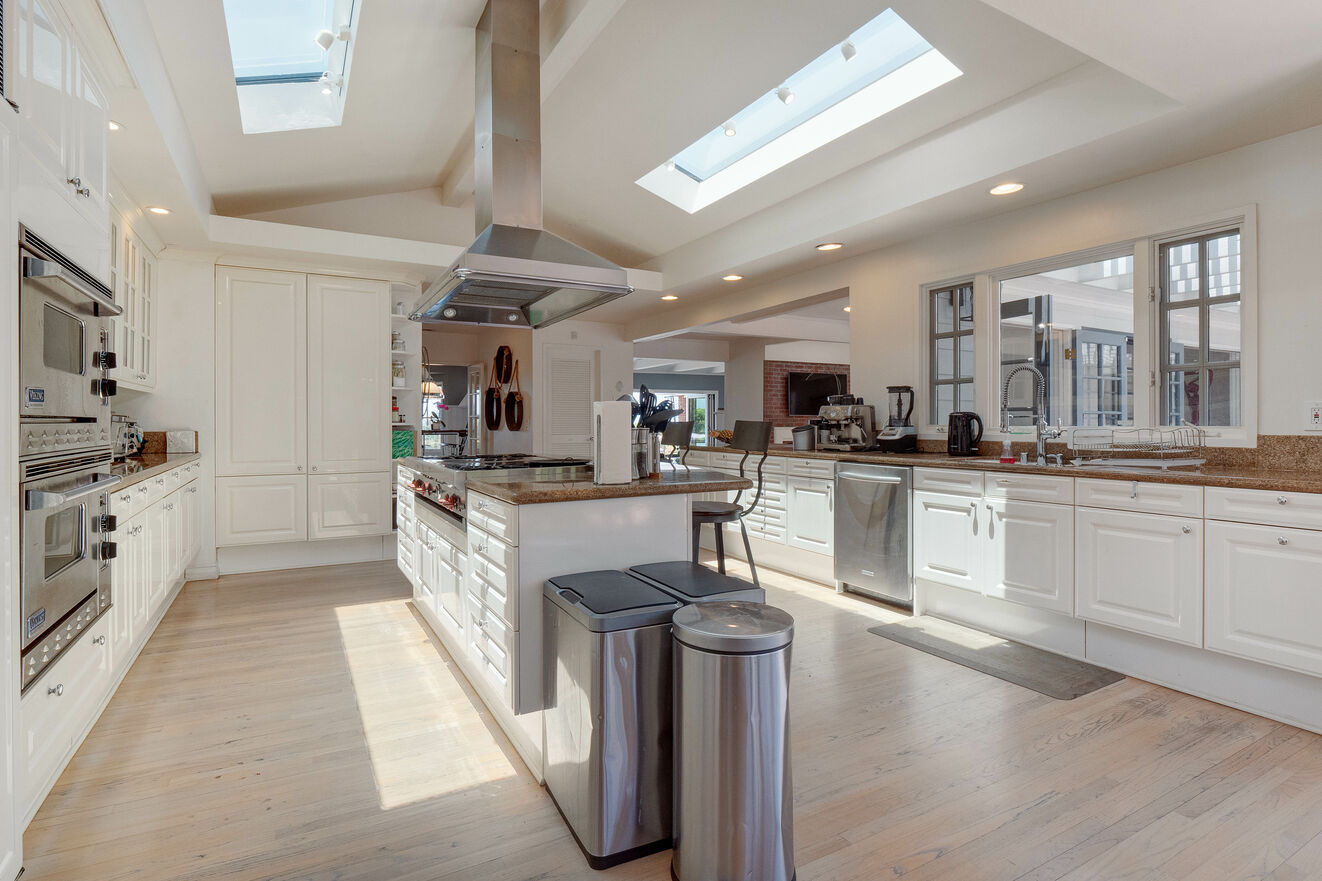Spacious open kitchen with professional grade Viking and Sub Zero appliances, bar seating for 6, open to dining / living areas and french doors to the pool and outdoor kitchen