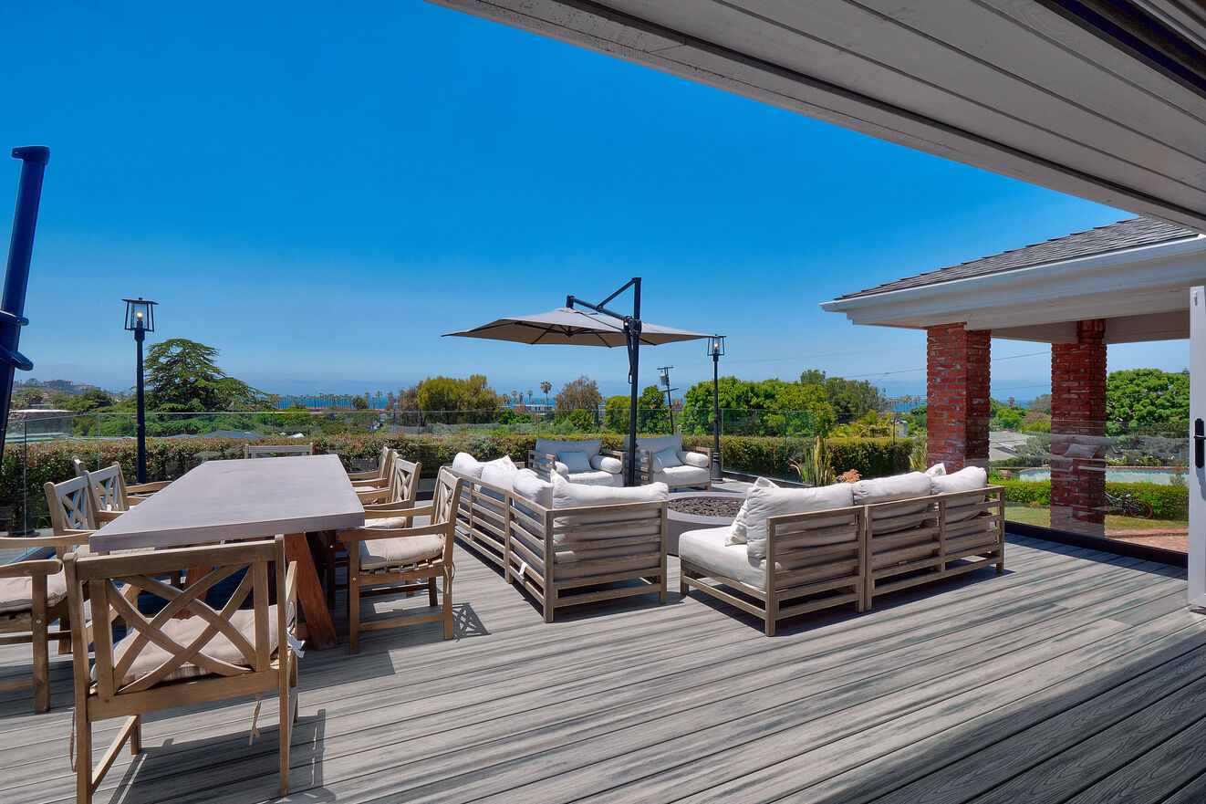 Front deck off the living room with plenty of patio furniture, shade, firepit and dining table for 8