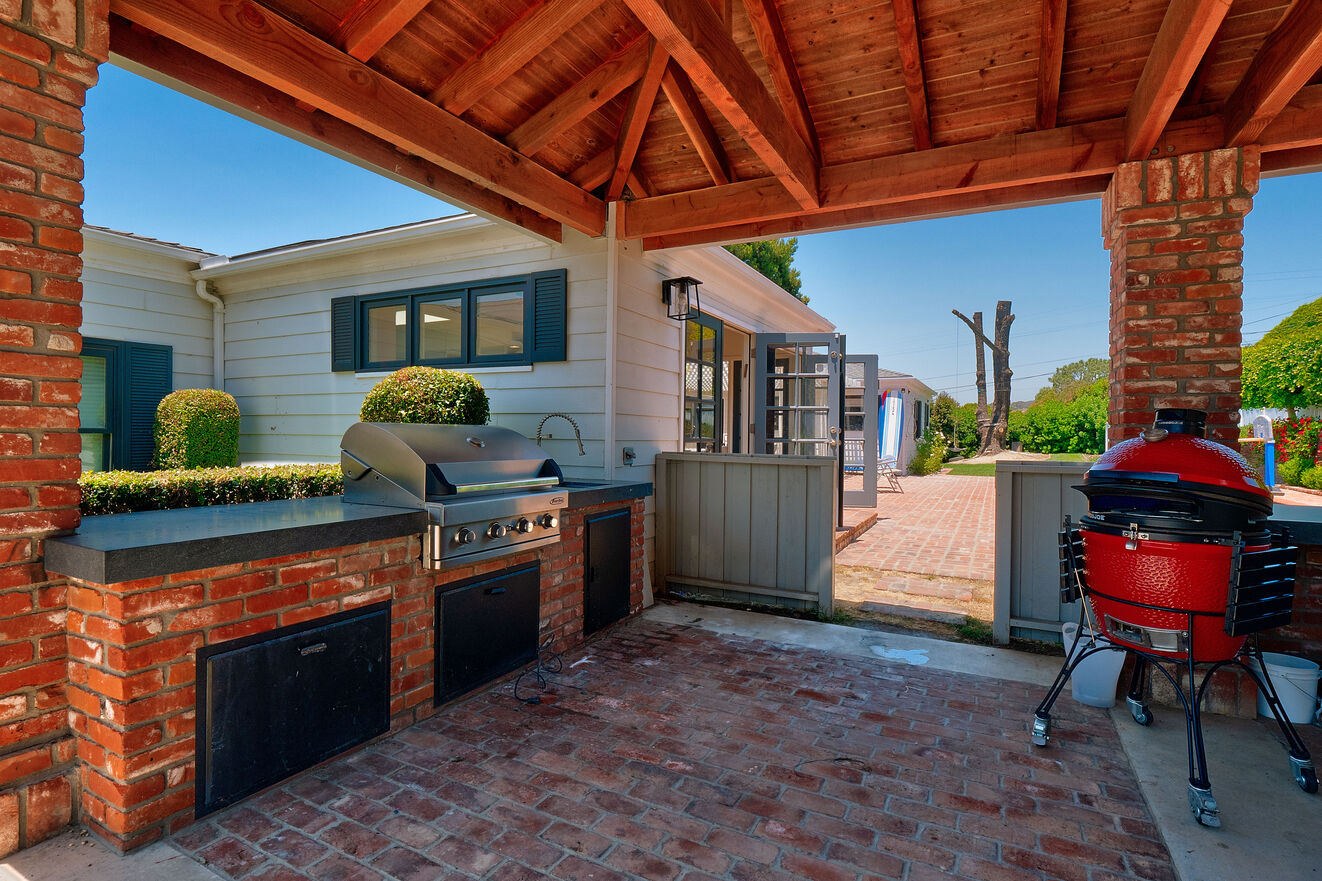 Outdoor kitchen with BBQ, smoker, sink, bar area and refrigerator