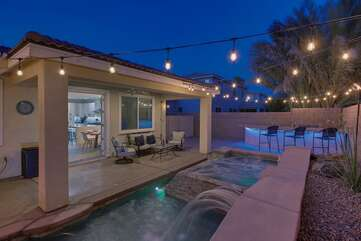 The covered patio features string lights, a relaxing waterfall, patio furniture, a built in BBQ and three high top chairs. Plenty of room to spread out!