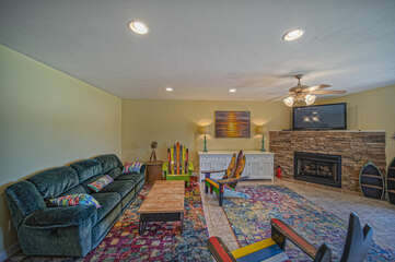 Ample seating of a living area with fireplace and TV.