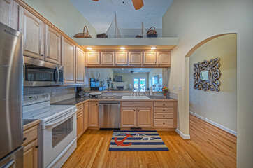 A colorful nautical mat and decor surrounds the kitchens stainless steel appliances.