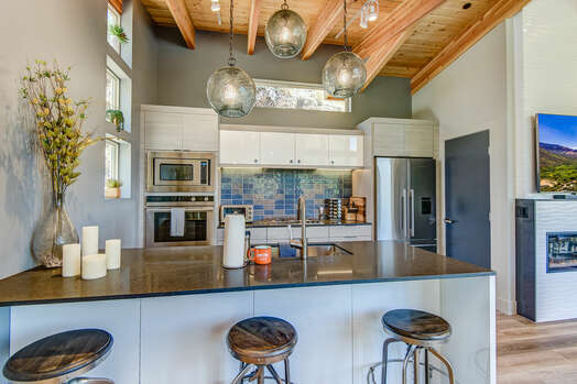 Gourmet Kitchen with Stone Countertops and Island Seating for Three