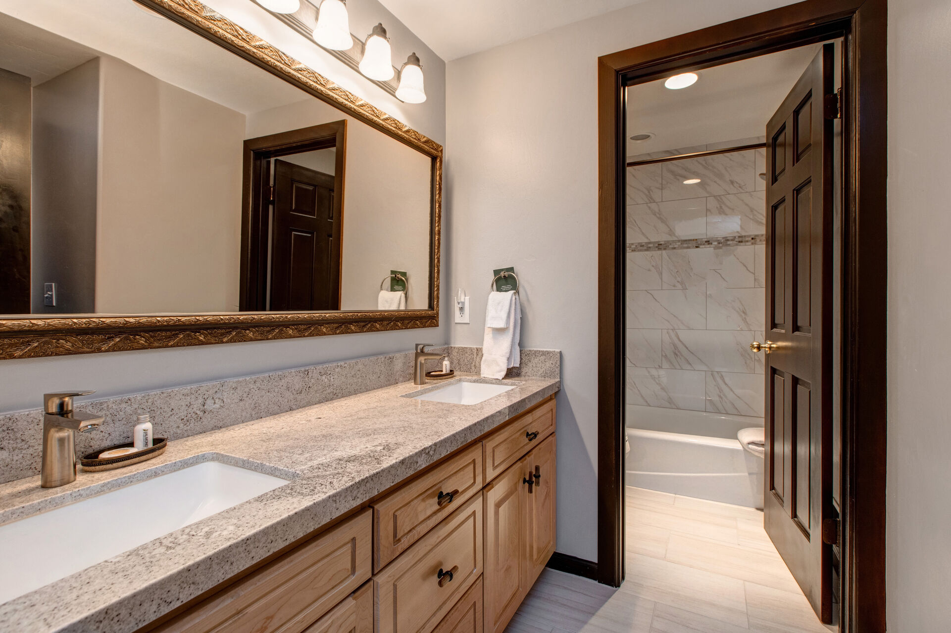 Lower Level Full Shared Bath with Dual Stone Counter Sinks and a Separate Tub/Shower Combo