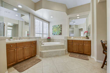 Private, en suite bathroom features a soaking tub, tile shower, two vanity sinks, and a makeup counter.