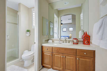 The private, en suite bathroom features a tile shower and a vanity sink.