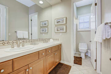 Jack and Jill bathroom serves Bedroom four and five and features a tub and tile shower combo and double vanity sinks.