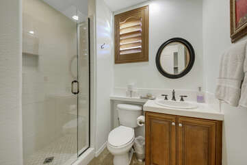 Private, en suite bathroom features a tile shower and vanity sink.