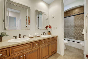 The hallway bathroom is located across from bedrooms 5 and 6 and features a double vanity sink and a combo shower/tub.