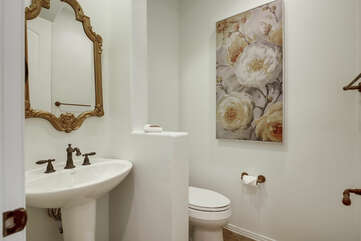 The hallway powder room is located across from the hallways closets and features a pedestal sink.
