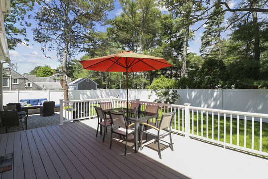 Back deck with plenty of seating looks on to patio with more seating. Nice fenced in yard.-16 Middleton Drive West Harwich Cape Cod -New England Vacation Rentals