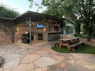 Our outdoor kitchen with newly added TV is where you'll enjoy wining and dining when it's sunny and warm.