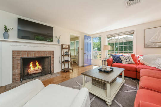 Living room with fire place, flat screen TV and ample seating to unwind! Deck entrance and bedroom #1 are off the living area- 80 Lienau Dr Chatham Ma - Cape Cod- New England Vacation Rentals