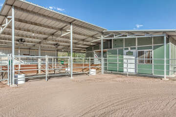 Two covered, matted, 12 x 15 ft stalls, each with its own fan and access to turn out area, await your horses.