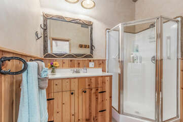 Private full bath has a vanity with sink and stall shower plus towels.