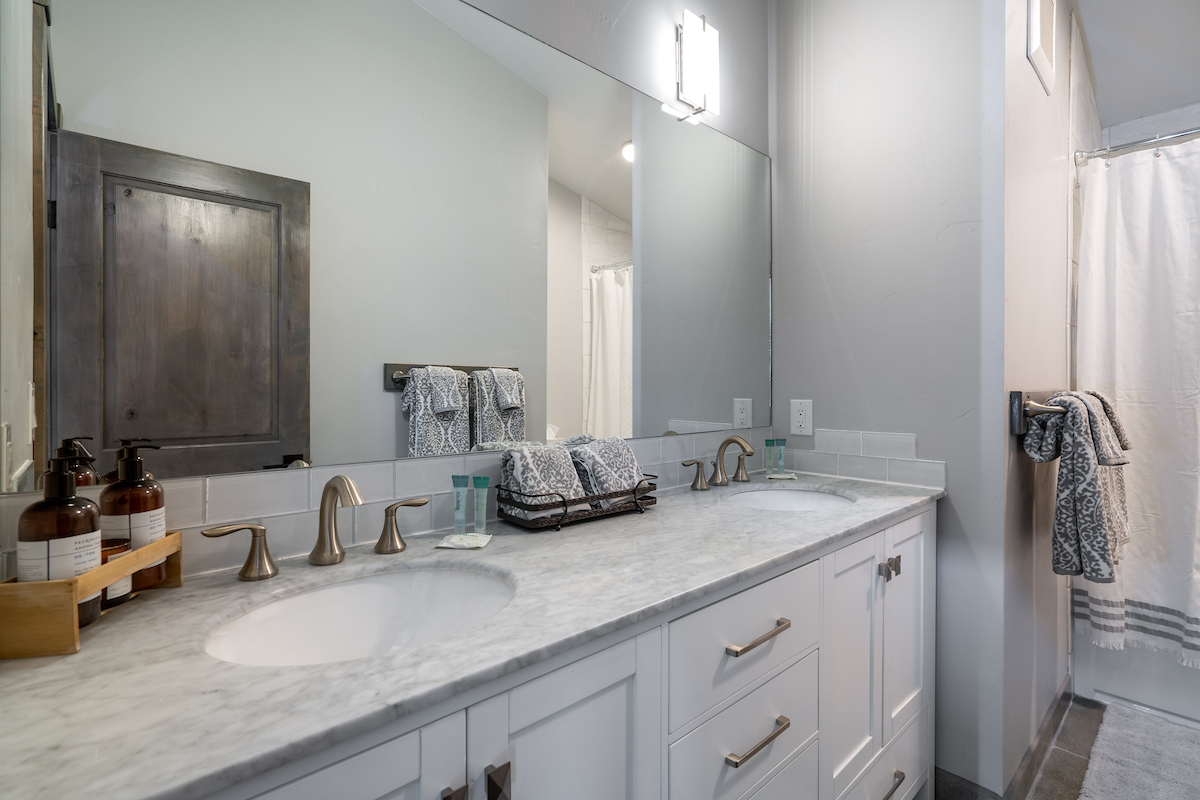 Upper level full bathroom with double sinks and a shower/tub combo.