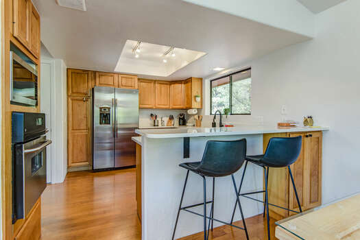 Kitchen Bar Seating for Two and Stainless Steel Appliances, Including a Wall Oven and Microwave