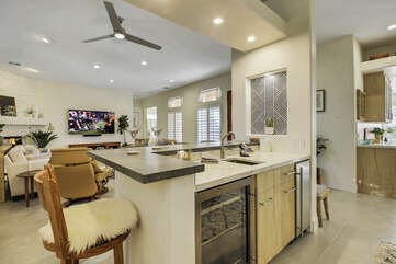 The wet bar includes an independent ice maker, a sink, and a wine refrigerator.