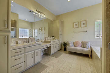The private, en suite bathroom features a Jacuzzi tub, tile shower, small bench seat, and his and her sinks on opposite sides of a vanity.